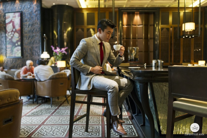 Anthony Pang takes a sip of coffee while looking absolutely suave in Sacoor Brothers.